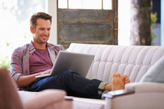 Man Relaxing On Sofa At Home Using Laptop Computer royalty free stock photos