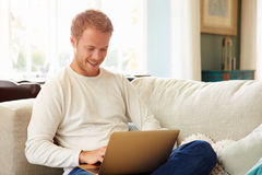 Man Relaxing On Sofa At Home Using Laptop Computer Royalty Free Stock Images