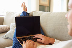 Man Relaxing On Sofa At Home Using Laptop Computer Stock Photography
