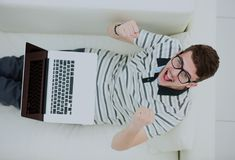 Man Relaxing on Sofa with Laptop Computer. Young man relaxing on the sofa with a laptop Royalty Free Stock Image
