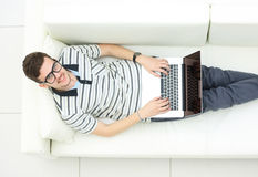 Man Relaxing on Sofa with Laptop Computer Stock Images