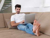Man Relaxing On Sofa With Laptop Royalty Free Stock Photos