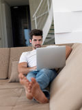 Man Relaxing On Sofa With Laptop Stock Photography