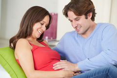 Man Relaxing On Sofa With Pregnant Wife At Home Stock Photos