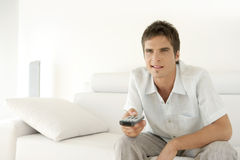 Man Relaxing on Sofa with Remote Stock Photos