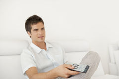 Man Relaxing on Sofa with Remote Royalty Free Stock Photos