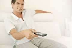 Man Relaxing on Sofa with Remote Royalty Free Stock Images