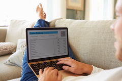 Man Relaxing On Sofa Using Internet Banking On Laptop Computer Royalty Free Stock Images