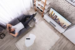 Man Relaxing On Sofa Watching Television stock image