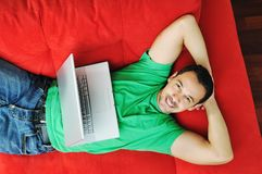 Man relaxing on sofa and work on laptop computer. Young man relax on red sofa and work on laptop at home indoor Royalty Free Stock Photo