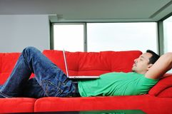Man relaxing on sofa and work on laptop computer royalty free stock photography