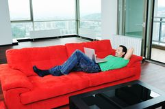Man relaxing on sofa and work on laptop computer stock photos