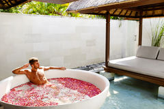 Man Relaxing In Spa Bath With Flowers Outdoors In Day Royalty Free Stock Images