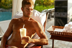 Man Relaxing At Spa With Cocktail Drink On Summer Vacations. Man Relaxing At Spa, Drinking Cocktail. Beautiful Handsome Healthy Happy Smiling Male With Sexy Body Stock Images