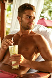Man Relaxing At Spa With Cocktail Drink On Summer Vacations. Man Relaxing At Spa, Drinking Cocktail. Beautiful Handsome Healthy Happy Smiling Male With Sexy Body Royalty Free Stock Image