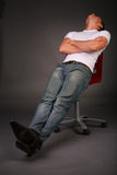 Man relaxing on stool Stock Image