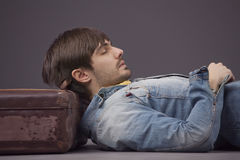 Man relaxing on suitcase Royalty Free Stock Photos