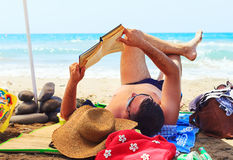 Man relaxing on the summer  beach reading Stock Photo