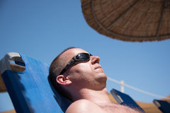 Man relaxing on a sun bed. Handsome man relaxing on a sun bed Royalty Free Stock Image