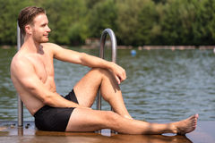 Man relaxing in the sun at public swimming pool Stock Photography
