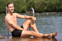 Man relaxing in the sun at public swimming pool Stock Photo