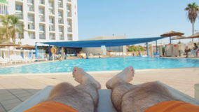 Man relaxing and sunbathing on sunbed by pool stock video footage