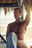 Man relaxing serenity at sunset. Beautiful Italian sexy model. Peace of mind at the beach. Royalty Free Stock Images