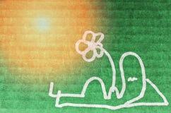 Man relaxing in sunshine drawn on green cardboard Stock Image