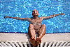 Man relaxing at the swimming pool stock images