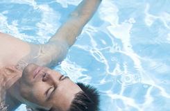A man relaxing in a swimming pool Stock Image