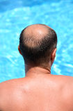 Man relaxing at the swimming pool, back Royalty Free Stock Photo