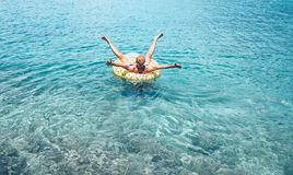Man relaxing when swims on inflatable pineapple pool ring in crystal clear sea water. Careless vacation concept image stock image