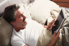 Man relaxing with tablet computer in bed. Royalty Free Stock Image