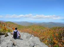 Man relaxing on top of the beautiful autumn mountain. Stock Photos