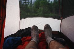 Wool socks of a man relaxing inside his tent campsite in the Adirondack Mountains. A man relaxing on top of his sleeping bag inside his tent. Adirondack royalty free stock photos