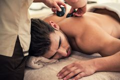 Man relaxing under the stimulating effects of a traditional hot stone massage Stock Photography