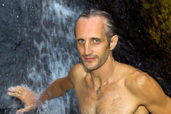 Man relaxing under waterfall. outside Stock Photo