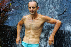 Man relaxing under waterfall. outside Stock Images