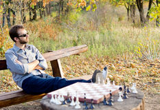 Man relaxing waiting for a chess opponent Royalty Free Stock Image