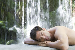 A man relaxing by a waterfall Royalty Free Stock Photography