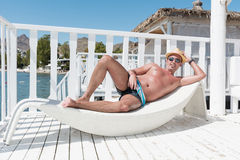Man relaxing on a white  sunbed  on the beach Royalty Free Stock Image