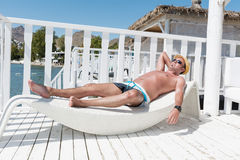 Man relaxing on a white  sunbed  on the beach Royalty Free Stock Images