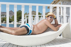 Man relaxing on a white  sunbed  on the beach Royalty Free Stock Photography