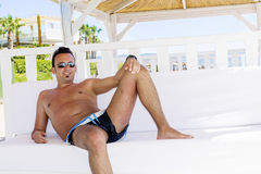 Man relaxing in a white  wooden bungalow on the beach Royalty Free Stock Image