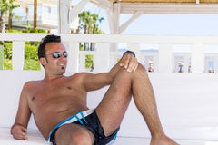Man relaxing in a white  wooden bungalow on the beach Royalty Free Stock Photo