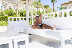 Man relaxing in a white  wooden bungalow on the beach Stock Photo