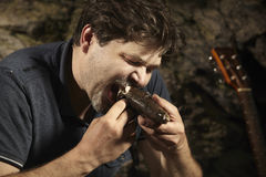 Man relaxing in wilderness and eating hunted fish. Man relaxing in wilderness with guitar and eating hunted fish stock photography