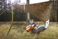 Man relaxing in wilderness with guitar in hammock. Man in wild forest making hammock bed and relaxing with guitar Stock Photography