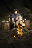 Man relaxing in wilderness with guitar and preparing hunted fish Stock Photos