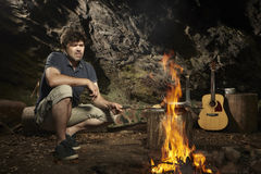 Man relaxing in wilderness and preparing hunted fish on fire. Man relaxing in wilderness with guitar and eating hunted fish royalty free stock photography